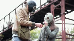 The guy with the girl in the gas masks smell the flower Stock Footage
