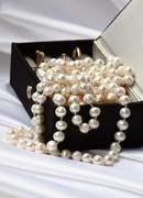pearls and rings in black jewelry box - stock photo