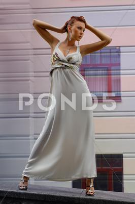 Stock photo of brunette in long dress near a hotel