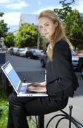 Happy businesswoman with laptop computer b Stock Photos