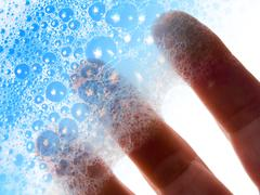 fingers hold blue soap bubbles - stock photo