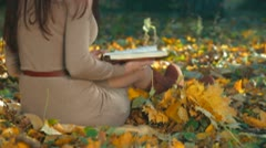 Student Reading Lecture Notes in Autumn Park Stock Footage