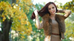 Young Woman Wearing Fur Vest in the Autumn Park Stock Footage