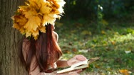 Stock Video Footage of Young Woman Reading a Book in Autumn Park
