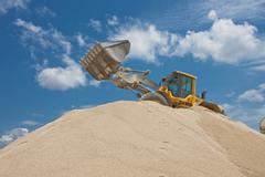 Yellow excavator on a construction site against blue sky Stock Photos