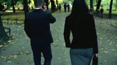 Business people walking in the park and talking on cellphone, steadicam shot - stock footage