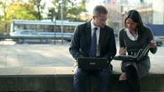 Business couple working with laptop and documents in the city, steadycam shot Stock Footage