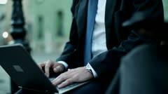 Businessman workingon laptop computer, outdoors Stock Footage