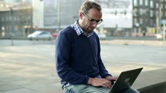 Young man finishing work on laptop and smiling to the camera, outdoors Stock Footage