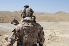 Back of alert soldier in full gear in the mountains of Afghanistan (HD)c Stock Photos