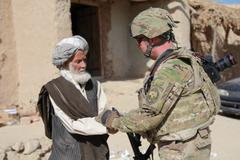 Soldier greeting native afghani man (HD)c Stock Photos