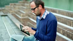 Portrait of young man with tablet computer sitting on the stairs, outdoors Stock Footage