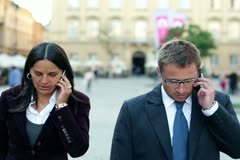 Business people getting bad news on cellphone, outdoors Stock Footage