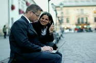 Business people sitting in the city and smiling to the camera, steadycam shot Stock Footage