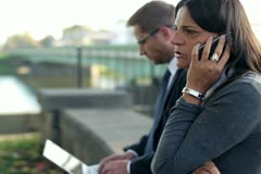 Business people with cellphone and laptop in the city, steadycam shot Stock Footage