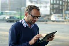 Man with tablet computer sitting in the city, steadicam shot Stock Footage