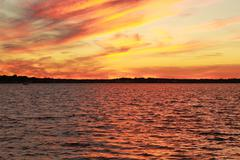 Colorful Red Sunset on the New Jersey Shore with rippling water - stock photo