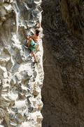 Rock Climber Climbing Up A Cliff - stock photo