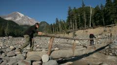 Walking on Log Bridge by Mount Rainier Stock Footage
