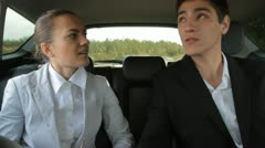 Young businesspeople talking on the back seats of car - stock footage