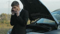 Young businessman smoking cigarettes and talking on the phone next to broken car - stock footage