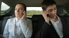 Young businesspeople talking on the phone on the back seats of car - stock footage