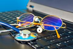 Stethoscope and glasses on black laptop Stock Photos