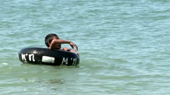 Asian Boy Playing With Inner Tube On The Ocean Stock Footage