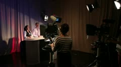 Television studio on air with presenters, cameras, lights and camera operators Stock Footage