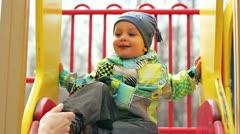 Boy sitting on children's slides - stock footage