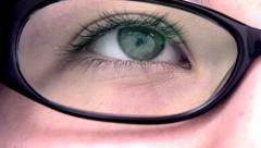 Extreme close up of an reading eye through the glasses. Stock Footage