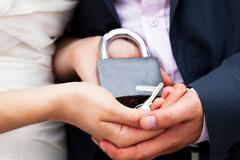 padlock with the chain in the hands of just married - stock photo