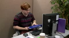 Teenage office worker struggling to find information in files Stock Footage