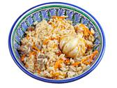 Stock Photo of traditional asian pilaf with garlic bulb in ceramic bowl