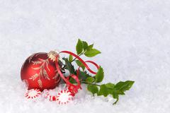 red Christmas ornament with holly , ribbon, and peppermint candy - stock photo