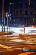 Strip from passing cars and traffic lights at night street Stock Photos
