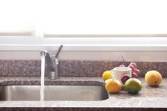 Cup, fruits and faucet on the kitchen Stock Photos