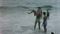 Happy COUPLE PLAYS AT THE BEACH 1960s Vintage Retro Amateur Film Home Movie 5320 Stock Footage