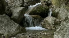 Creek flowing amongst rocks Stock Footage