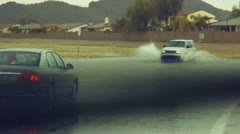 Traffic on a flooded street in a desert neighborhood after a storm. Stock Footage