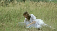 Girl typing on a computer in a field Stock Footage