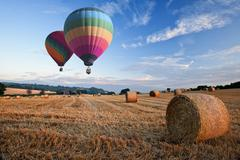 hot air balloons over hay bales sunset landscape - stock photo