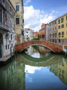 beautiful reflections of bridge in canal in venice italy - stock photo
