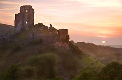 Romantic fantasy magical castle ruins against stunning vibrant sunrise Stock Photos