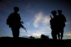 Silhouette of modern soldiers against sunset wky with military vehicles Stock Photos