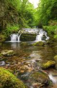 stunning waterfall flowing over rocks through lush green forest with long exp - stock photo