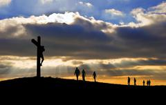 Jesus christ crucifixion on good friday silhouette with people walking uphill Stock Photos