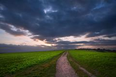 countryside landscape path leading through fields towards dramatic beautiful - stock photo