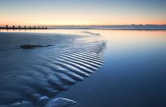 Beautiful low tide beach vibrant sunrise Stock Photos