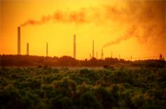 Industrial chimney stacks in natural landscape polluting the air Stock Photos